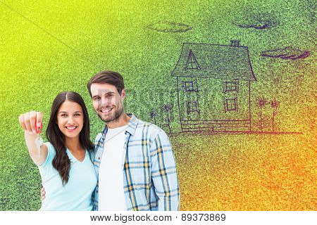 Happy young couple showing new house key against astro turf surface