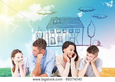 Family lying with head in hands against blue sky over green field