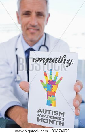 The word empathy and portrait of a male doctor showing a blank prescription sheet against autism awareness month