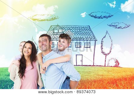 Happy parents giving piggyback ride to children while looking up against blue sky over green field