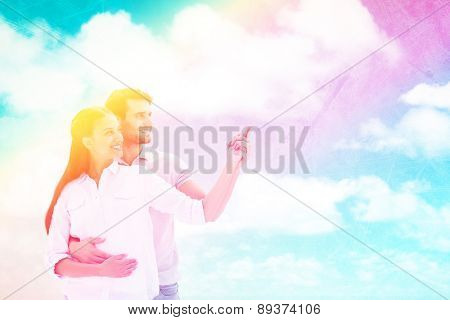Cute couple embracing and pointing against painted sky