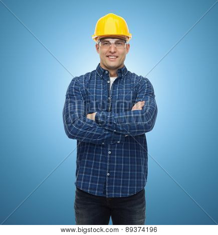 repair, construction, building, people and maintenance concept - smiling male builder or manual worker in helmet over blue background