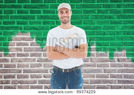 Happy man with paint roller standing arms crossed against red brick wall