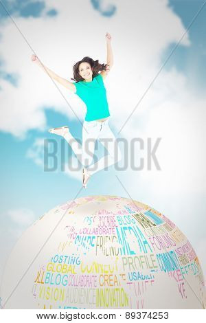 Pretty brunette jumping and smiling against blue sky