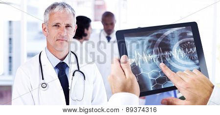 Man using tablet pc against mature doctor pointing at something on his clipboard
