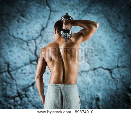 sport, fitness, weightlifting, bodybuilding and people concept - young man with dumbbell flexing biceps over concrete wall background from back