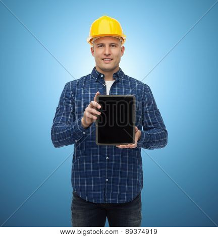 repair, construction, building, people and maintenance concept - smiling male builder or manual worker in helmet showing tablet pc computer blank screen over blue background