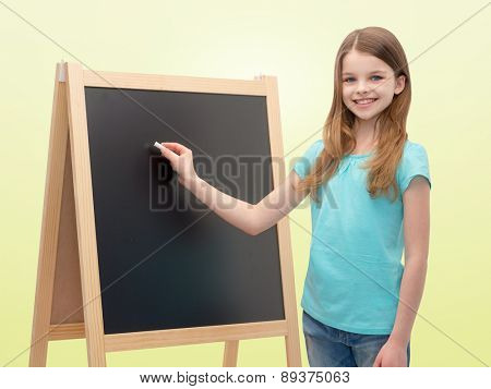 people, school, children, advertisement and education concept - happy little girl with blackboard and chalk over yellow background