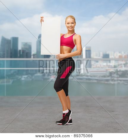 sport, fitness, people and advertisement concept - happy smiling sportswoman with white blank board over city waterside background