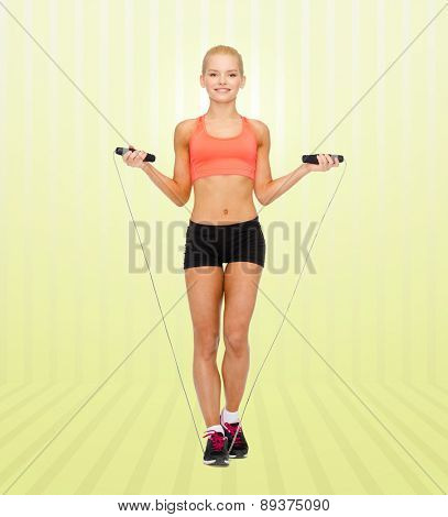 sport, fitness, people and weight loss - smiling sporty woman jumping  with skipping rope over yellow striped background