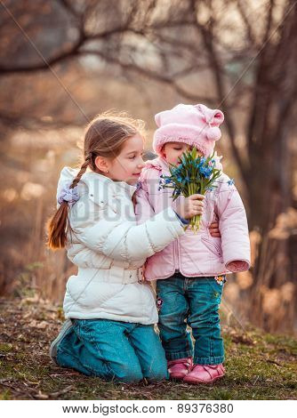 happy little sisters with  a bouquet of flowers