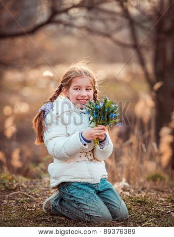 happy cute little girl in the forest holding a bouquet of snowdrops