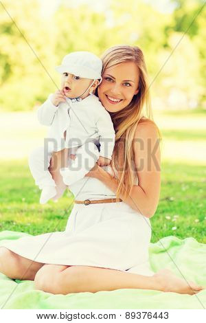 family, child and parenthood concept - happy mother with little baby sitting on blanket in park