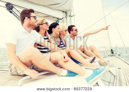 vacation, travel, sea, friendship and people concept - smiling friends sitting on yacht deck and pointing finger