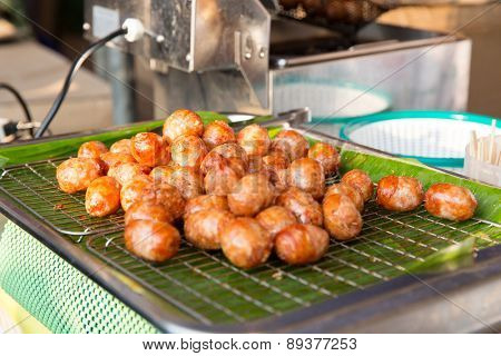 cooking, asian kitchen, sale and food concept - fried meatballs sale at street market