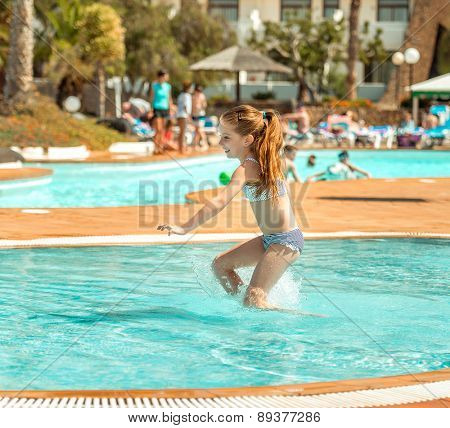 little girl with long hair playing in the pool