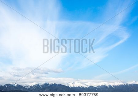 Mountains peaks and blue sky with clouds background