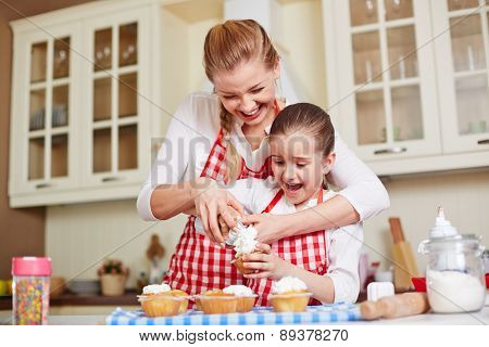 Young woman showing her daughter how to decorate baked muffins with whipped cream