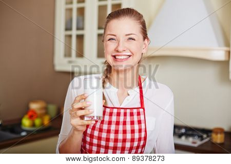 Happy and healthy woman with glass of kefir looking at camera