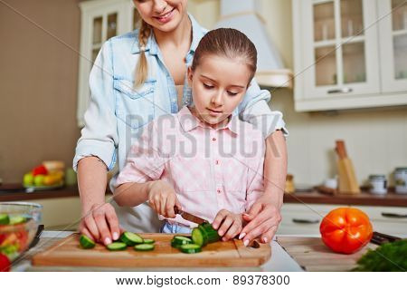 Little girl cutting fresh cucumber with her mother near by