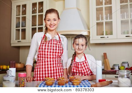 Pretty girl and her mother looking at camera with baked muffins on table near by