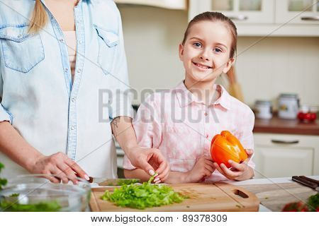 Happy little girl with pepper looking at camera while her mother cutting lettuce near by
