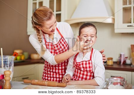 Laughing girl and her mother in aprons having fun in the kitchen