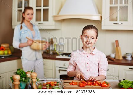 Little girl looking at camera while cutting pepper with her mother on background