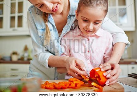 Little girl cutting fresh pepper with help of her mother
