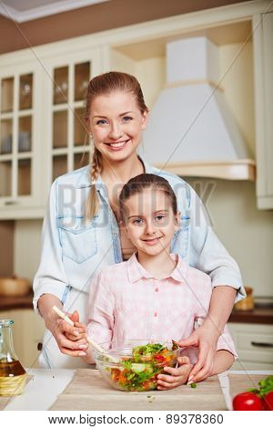 Young female and cute girl with bowl of vegetable salad looking at camera in the kitchen