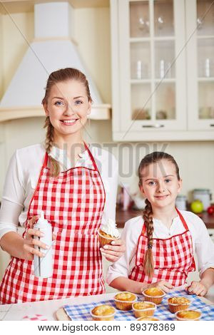 Pretty child and her mother with baked muffin decorated with cream looking at camera