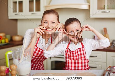 Ecstatic girl and her mother in aprons keeping ends of their pigtails by noses
