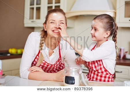 Little girl smutching her mother face with flour in the kitchen