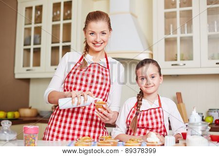 Young woman decorating baked muffin with cream and her daughter near by