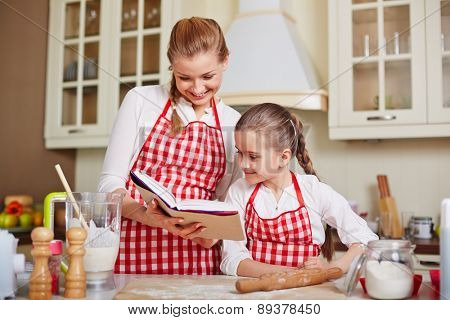 Cute girl and her mother reading how to make dough at home