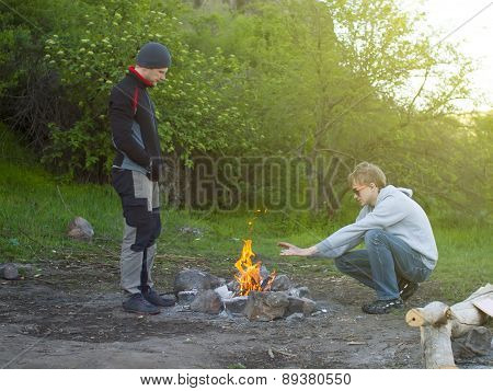Two Men Warming Themselves By The Fire.