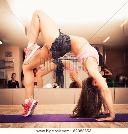 Woman Doing Exercises On Mat In Gym