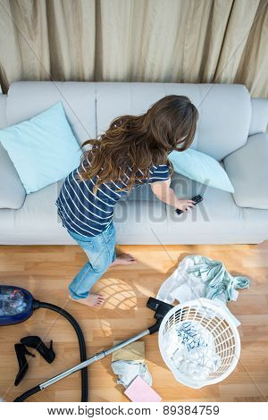 Pretty brunette cleaning the living room at home