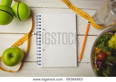 Notepad with indicators of healthy lifestyle on wooden table
