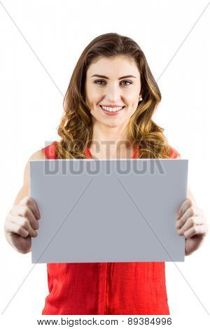Pretty brunette showing a card on white background