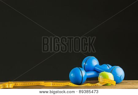 Blue dumbbells with green apple and measuring tape on wooden background