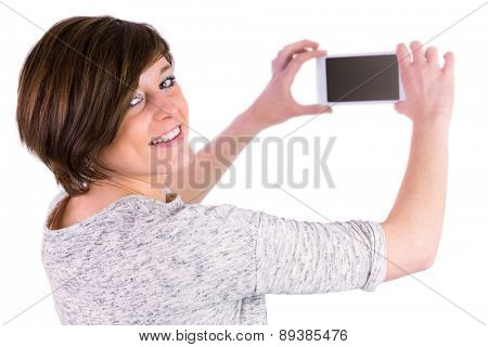 Pretty brunette looking at camera and taking a picture with her smartphone on white background