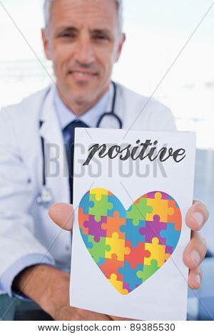 The word positive and portrait of a male doctor showing a blank prescription sheet against autism awareness heart