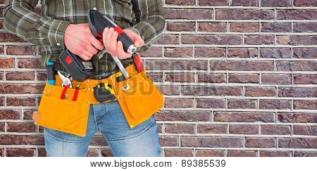 Manual worker holding gloves and hammer power drill against red brick wall