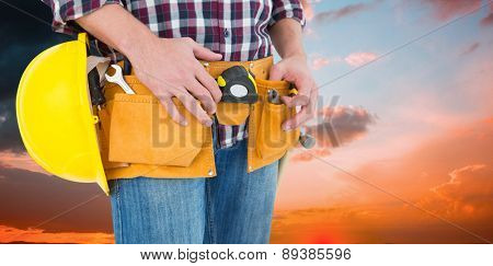 Handyman with tool belt and handyman against orange and blue sky with clouds