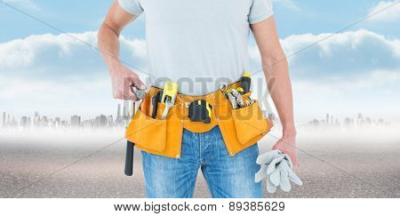 Technician holding gloves and hammer against city on the horizon