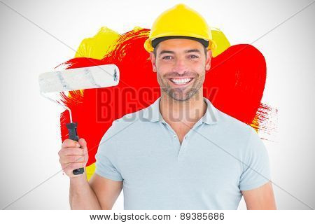 Portrait of manual worker holding paint roller against red and yellow paint
