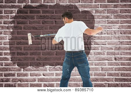 Man using paint roller on white background against red brick wall