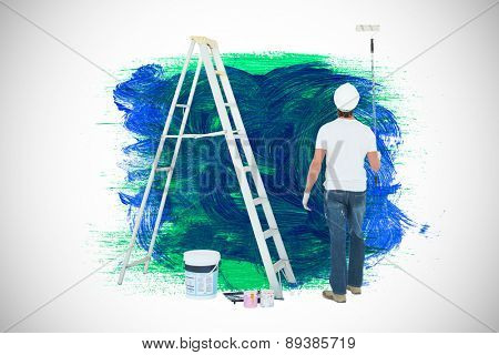 Man with paint roller standing by ladder against blue and green paint