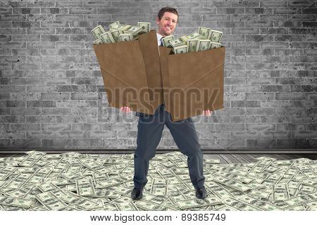 Businessman carrying bags of dollars against grey room